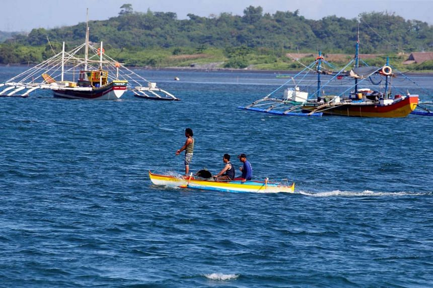 Fishermen ride on a small boat past their big boats as they prepare to fish at disputed Scarborough Shoal, at the coastal village of Cato in Infanta, Pangasinan in the Philippines, Nov 3, 2016.