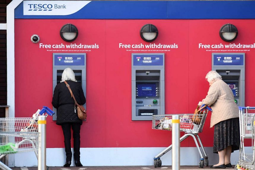 Customers use RBS branded automated teller machines (ATMs) at a Tesco Bank cash point, in Liverpool, north west England, on Nov 7, 2016.