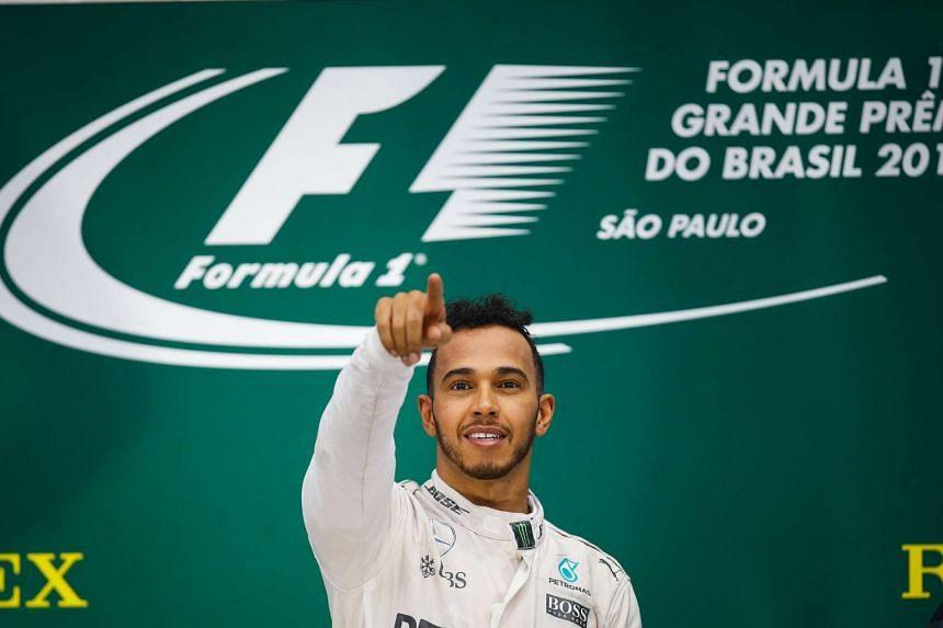 British Formula One driver Lewis Hamilton, of Mercedes, celebrates after winning the Formula One Grand Prix of Brazil.