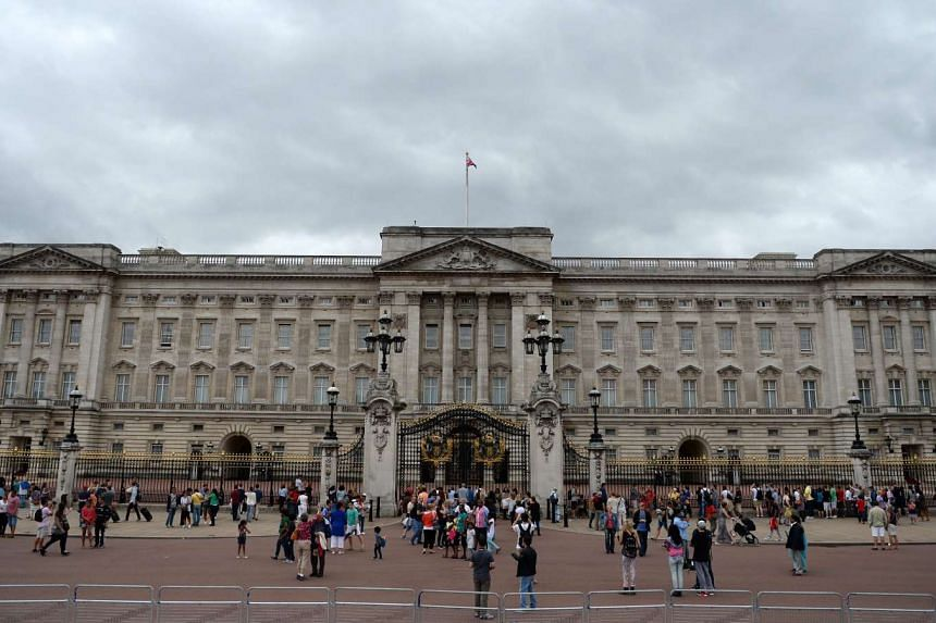 A file photograph showing people stand outside of Buckingham Palace in London on July 31, 2013.