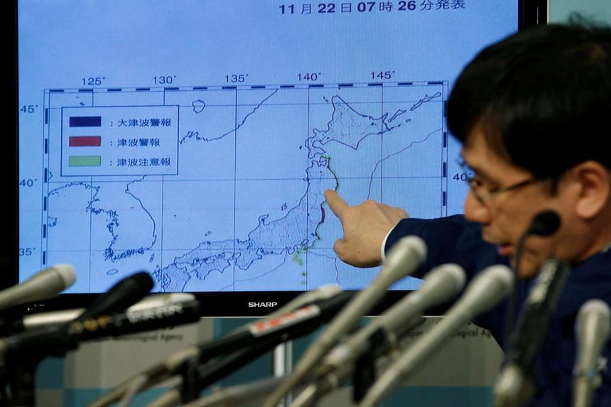 Japan Meteorological Agency's earthquake and volcano observations division director Koji Nakamura points at a map showing earthquake information during a news conference on Nov 22, 2016.