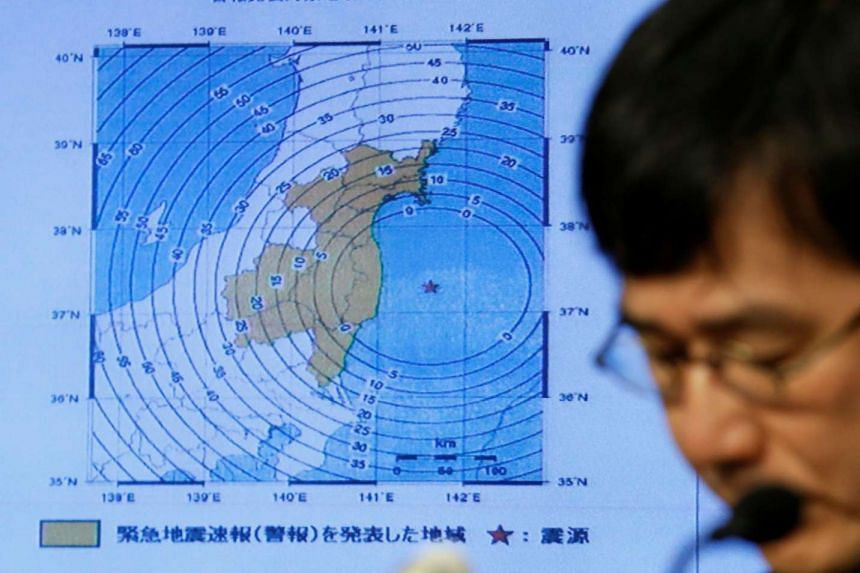 Japan Meteorological Agency's earthquake and volcano observations division director Koji Nakamura addresses a news conference next to the map showing an earthquake epicentre off the coast of Fukushima prefecture, on Nov 22, 2016.