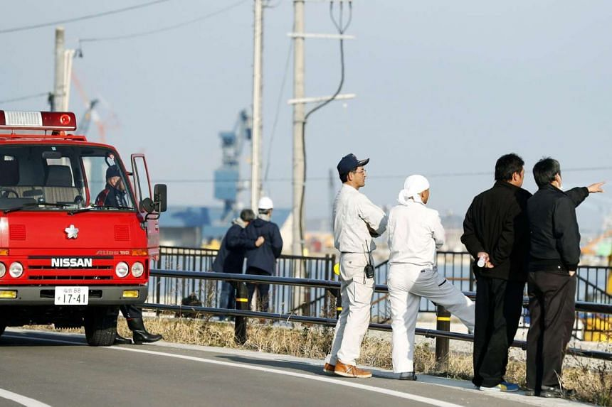Firefighters and local residents look toward the port to check the water level after tsunami advisories were issued following an earthquake in Soma, Fukushima prefecture, on Nov 22, 2016.