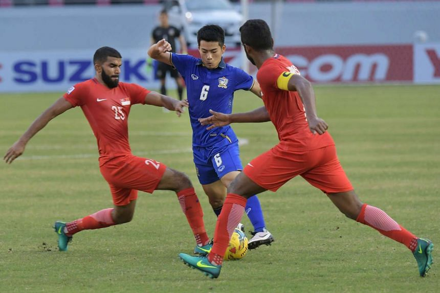 Thailand's Sarach Yooyen checked by Anumanthan Kumar and Hariss Harun (right) during the Suzuki Cup 2016 match between Singapore and Thailand at the Philippines Sports Stadium on Nov 22, 2016.
