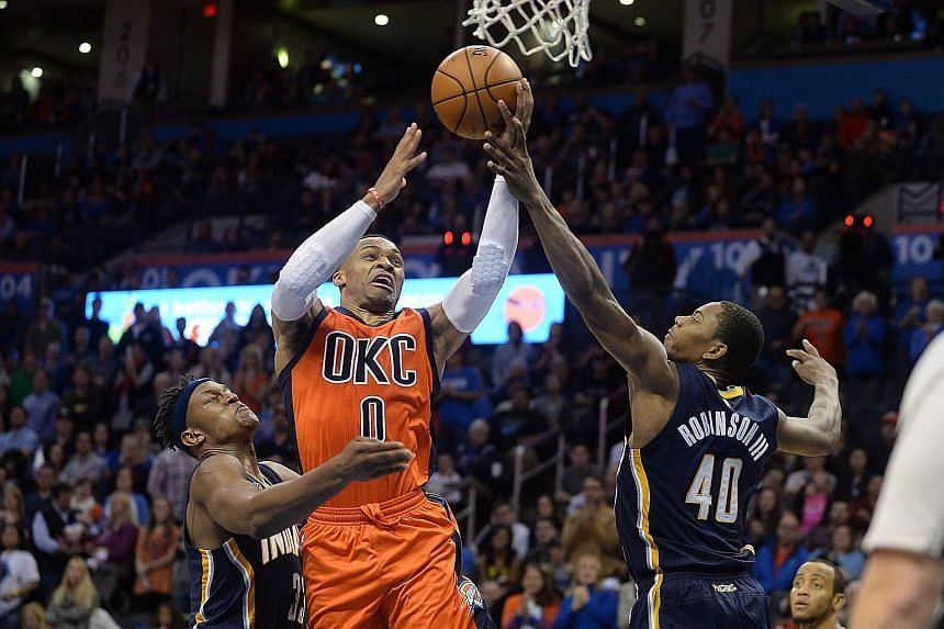 Thunder guard Russell Westbrook drives to the basket between the Pacers' Myles Turner and Glenn Robinson during the fourth quarter.