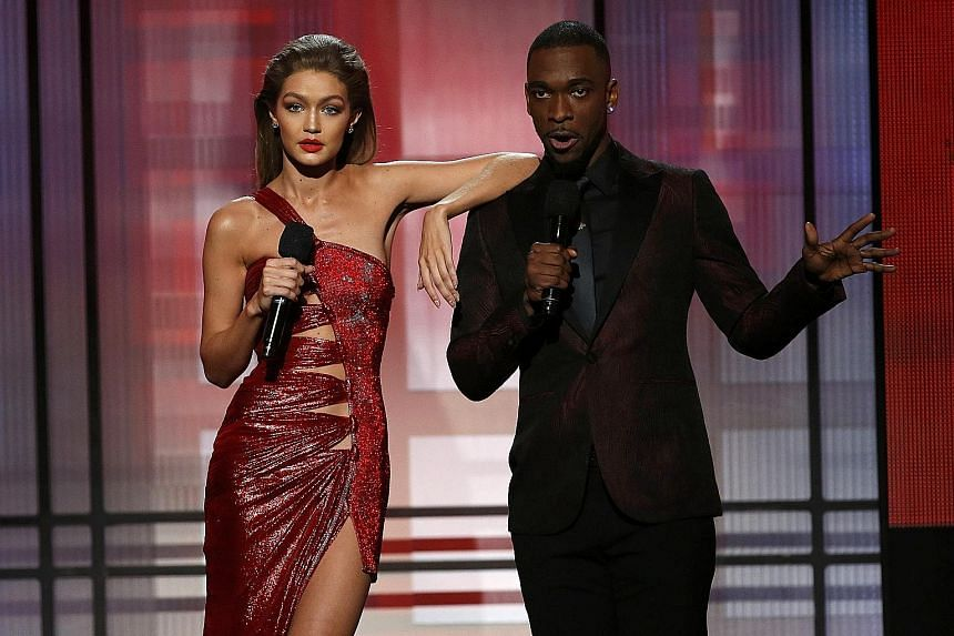 Hosts of the American Music Awards Gigi Hadid and Jay Pharoah (both above) took a dig at President-elect Donald Trump and his wife Melania while Green Day's frontman Billie Joe Armstrong slammed Mr Trump during the band's performance.