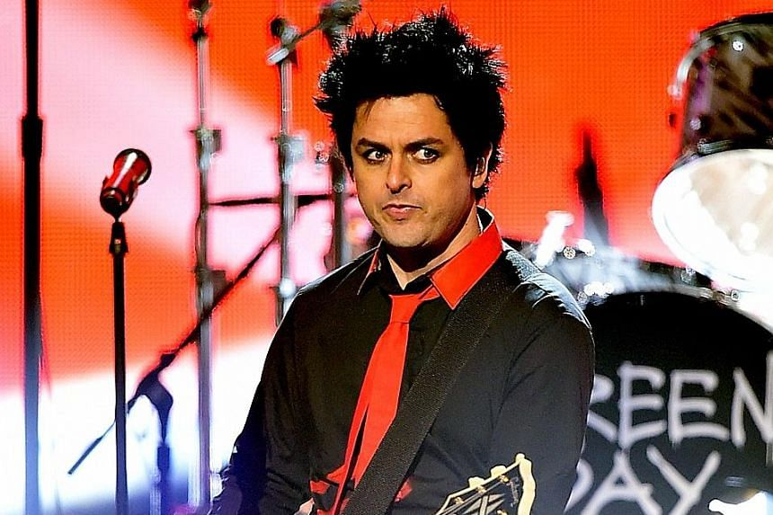 Hosts of the American Music Awards Gigi Hadid and Jay Pharoah took a dig at President-elect Donald Trump and his wife Melania while Green Day's frontman Billie Joe Armstrong (above) slammed Mr Trump during the band's performance.