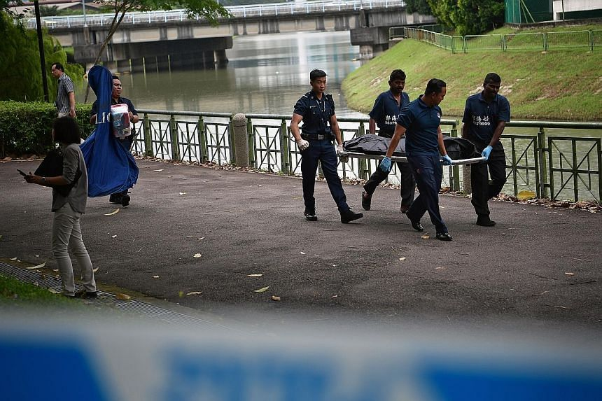 Right: The body of the woman, found floating in the Kallang River, being removed from the scene yesterday. Police have classified the case as an unnatural death. Above: Among the items removed from the scene was a pair of pink slippers.