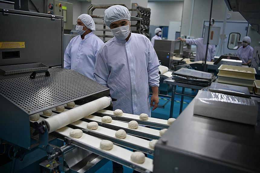 Employees operating an automated breadmaker at BHF. Automated processes have helped the firm to cut costs by about half.