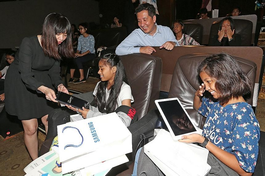 Ms Esther Low from Samsung showing the Galaxy Tab A tablet with S Pen to Hafiqah Nadia Mohd Azim (centre), 13, and Nurul Qistina Maisarah Sazaly, 14. With them is ST news editor Marc Lim.