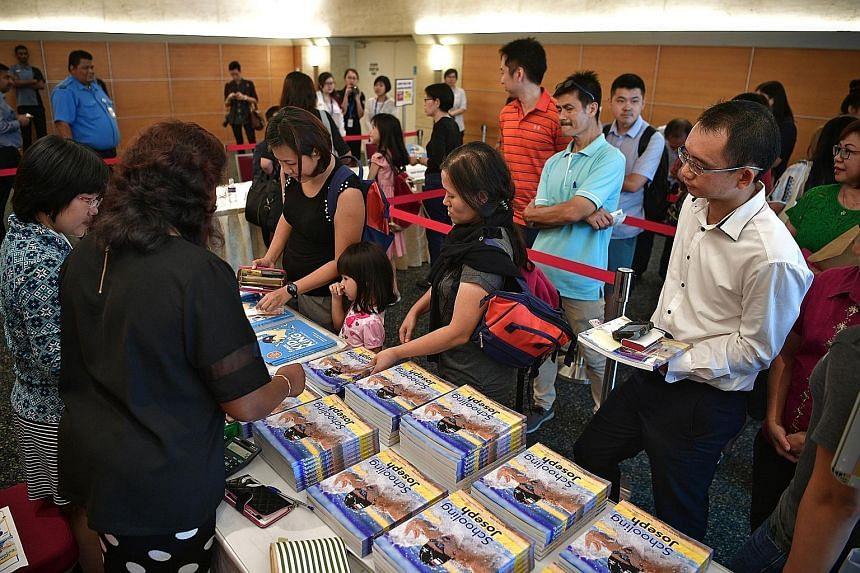 Fans of the swim star queueing to buy two authorised biographies, From Kid To King and Schooling Joseph, at the SPH News Centre yesterday. Olympic champion Joseph Schooling (in red) with ST news editor Marc Lim, who wrote From Kid To King, at the SPH