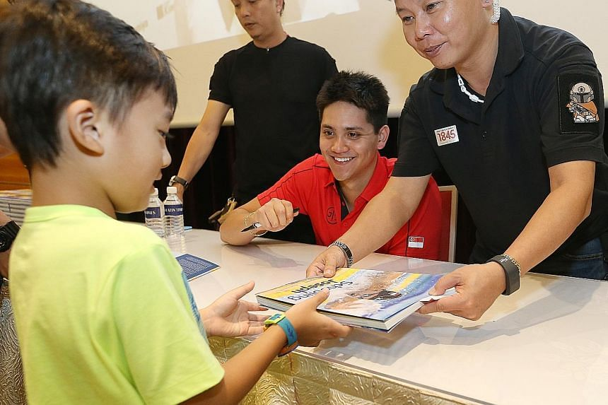 Six-year-old Jayden Kok getting his copy of a book on Olympic champion Joseph Schooling back after the star signed it at the Singapore Press Holdings News Centre yesterday. The 21-year-old swim star autographed copies of two books published by Strait