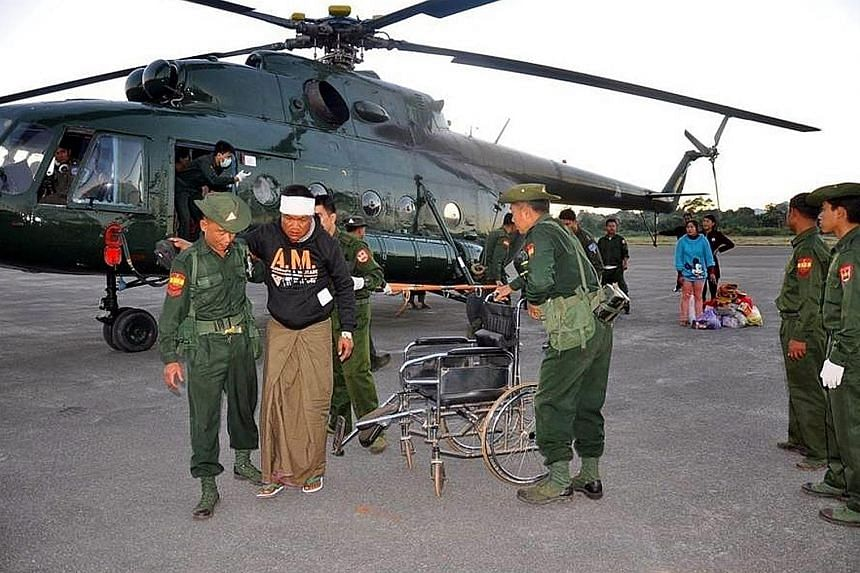 Myanmar soldiers helping an injured man in Shan state on Sunday. Eight people were killed when a coalition of northern rebels attacked military and police outposts on the border on Sunday.