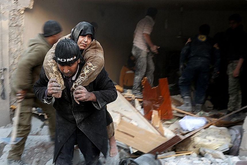 A woman being rescued from the rubble of a building following reported air strikes on Aleppo's rebel-held district of al-Hamra on Sunday.