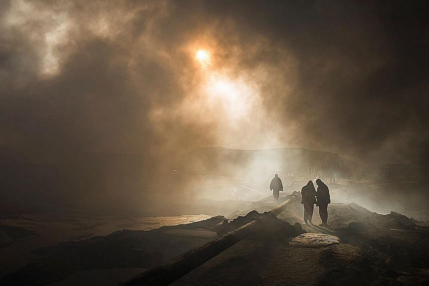 The sun is reduced to a mere glow by dense smoke as firefighters assemble a water pipeline in the town of Qayyarah, some 70km south of Mosul. Engineers, firefighters and policemen have been trying since August to put out fierce fires from oil wells s