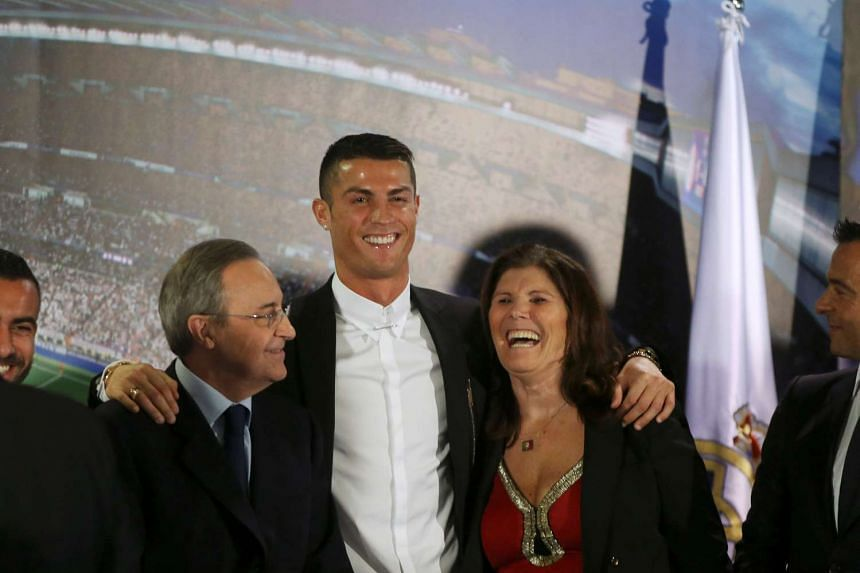 Real Madrid's Cristiano Ronaldo poses with his mother Dolores Aveiro and the club's president Florentino Perez after a ceremony for his contract enewal at Santiago Bernabeu stadium in Madrid, Spain, on November 7.