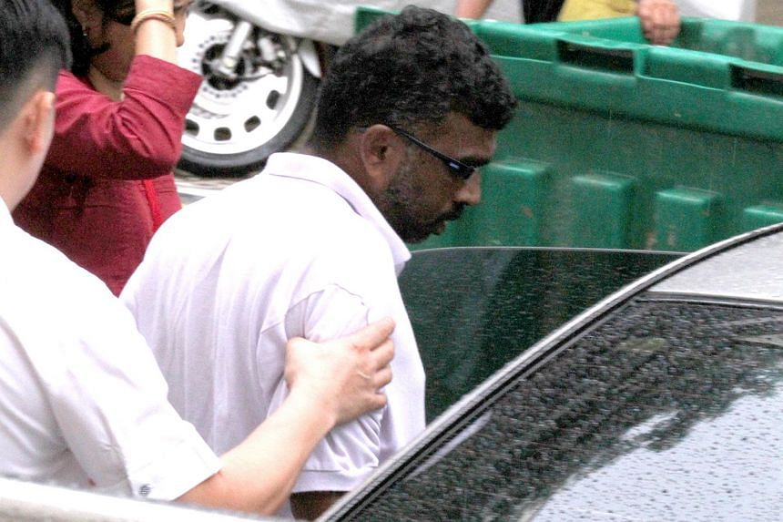 P. Mageswaran, who was charged in court on Dec 19, 2013, with causing the death of Madam Kanne Lactmy, being escorted back to the scene of the crime by the police on Dec 23, 2013.