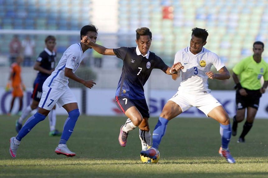 Park Mony Udom (centre) of Cambodia in action against Shahrul Mohd Saad (right) of Malaysia during the AFF Suzuki Cup Group B soccer match in Thuwanna Football statdium in Yangon on Nov 20, 2016.