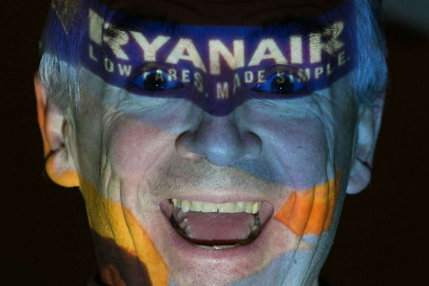 Ryanair chief executive Michael O'Leary poses with his company's logo projected on his face at a press conference in August 2016.