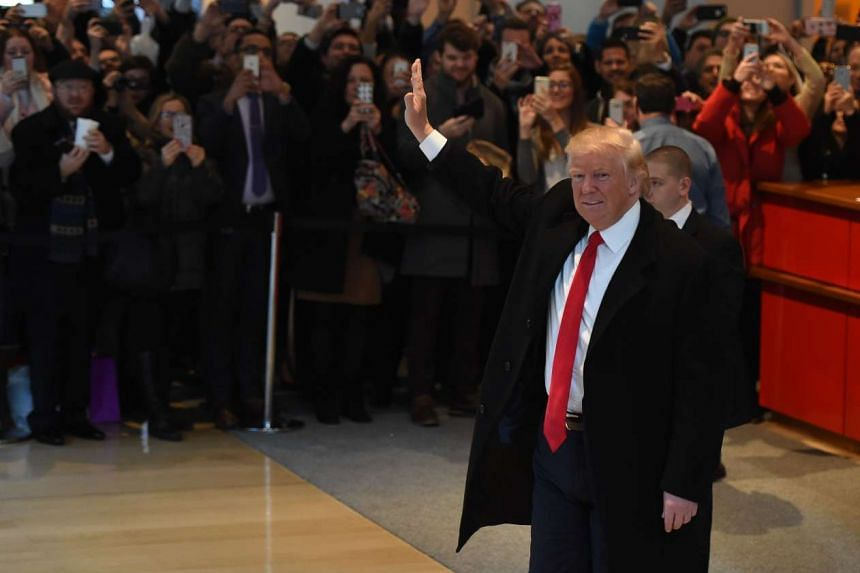 US President-elect Donald Trump waves to the crowd after leaving a meeting at the New York Times on Nov 22, 2016 in New York.