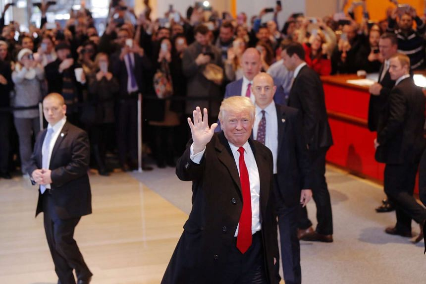 Trump reacts to a crowd gathered in the lobby of the New York Times building after a meeting in New York, Nov 22, 2016.