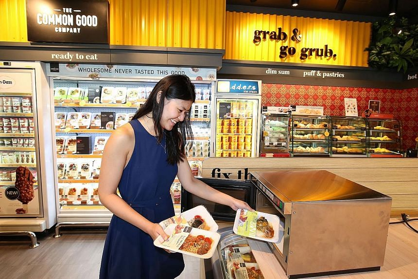 Public relations executive Gretchen Lee placing meals from Cheers' new ready-to-eat range into a microwave oven. The meals are packed in a new type of vacuum skin packaging, which is expected to preserve the flavour and aesthetics of the food.