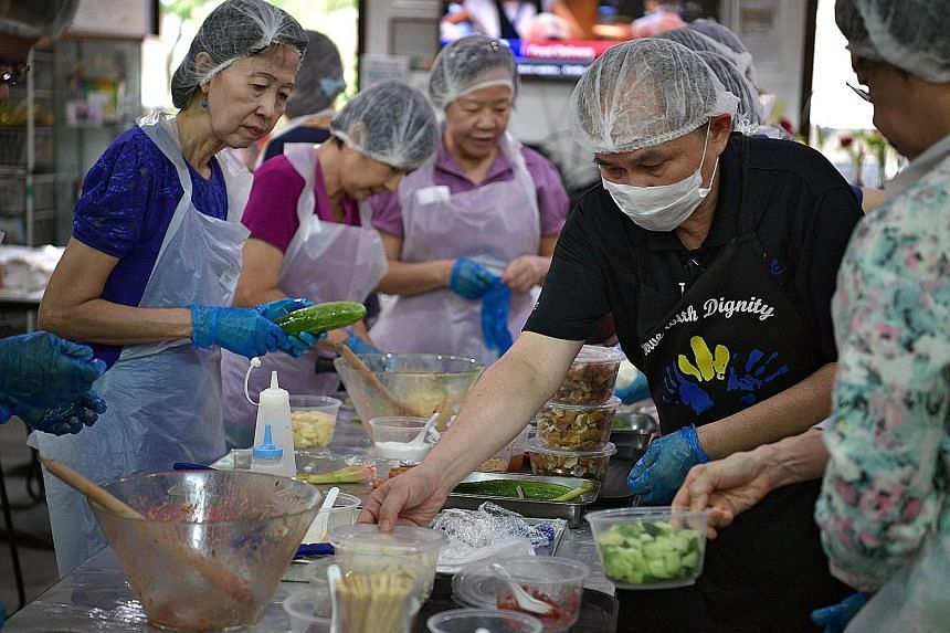 Mr Tiong showing participants including Ms Foong (left) how to make rojak at yesterday's workshop organised by Dignity Kitchen.