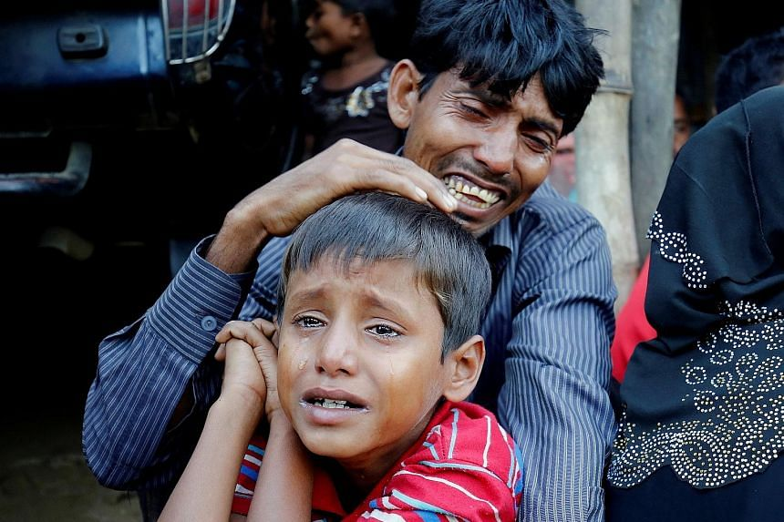 A distraught Rohingya Muslim man and his son after being caught by Border Guard Bangladesh troops while illegally crossing the Myanmar border.