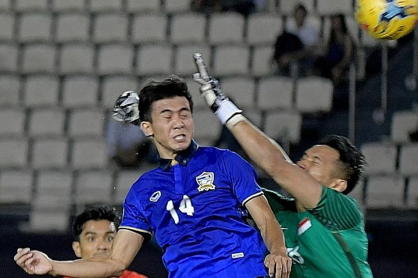 Thailand's Sarawut Masuk (No. 14) celebrating his winning goal with his skipper Teerasil Dangda after leaping the highest to head the game's only goal past Singapore goalkeeper Hassan Sunny.
