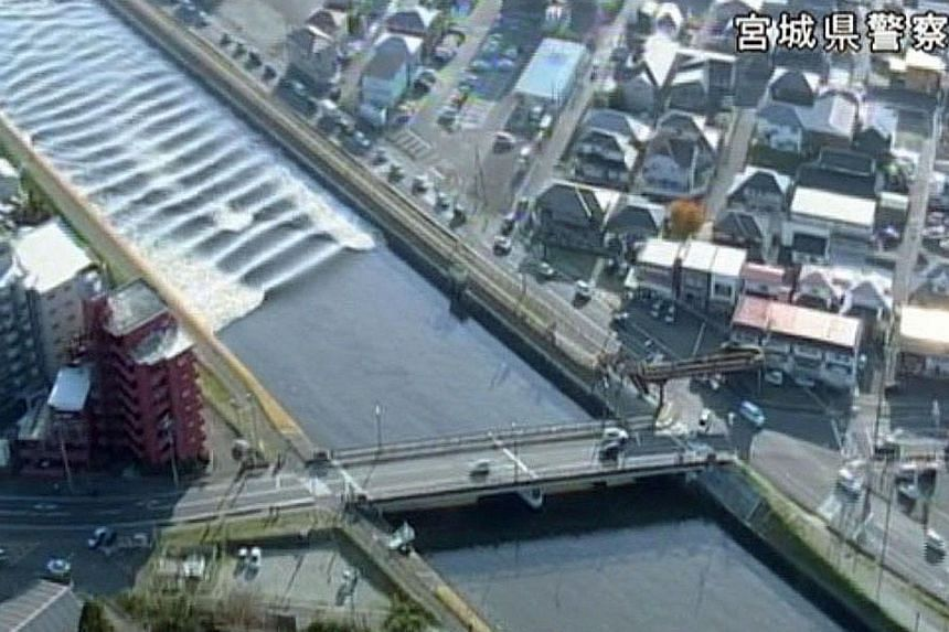 A tidal surge seen in the Sunaoshi River yesterday in this video grab image released by Miyagi Prefectural Police via Kyodo. Tsunami advisories were issued after the earthquake in Tagajo, Miyagi prefecture.