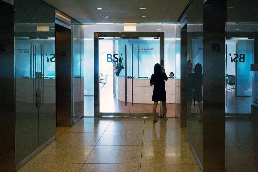 A woman types the entry code at the entrance to the BSI Bank Ltd. headquarters in Singapore, on May 24, 2016.