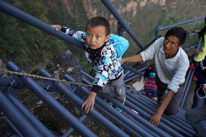 A young villager scales the new steel ladder on his way home from school.