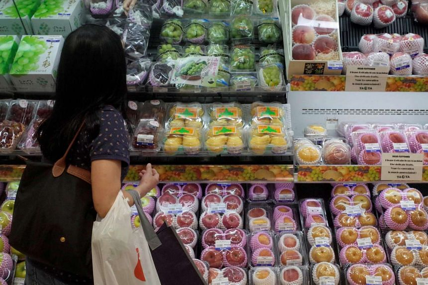 A woman shops for fruits at a supermarket in Singapore.