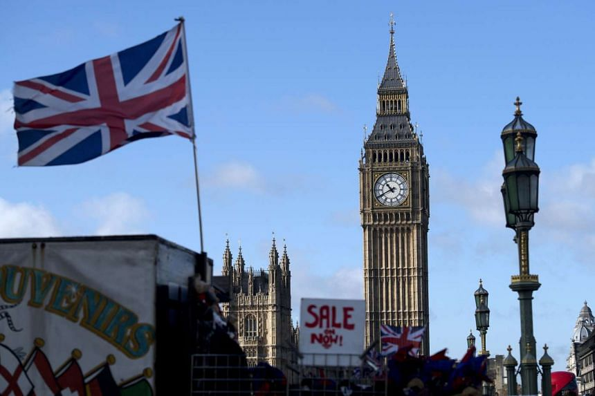 A Union flag flies from a flagpole near to the Elizabeth Tower at the Houses of Parliament in central London.