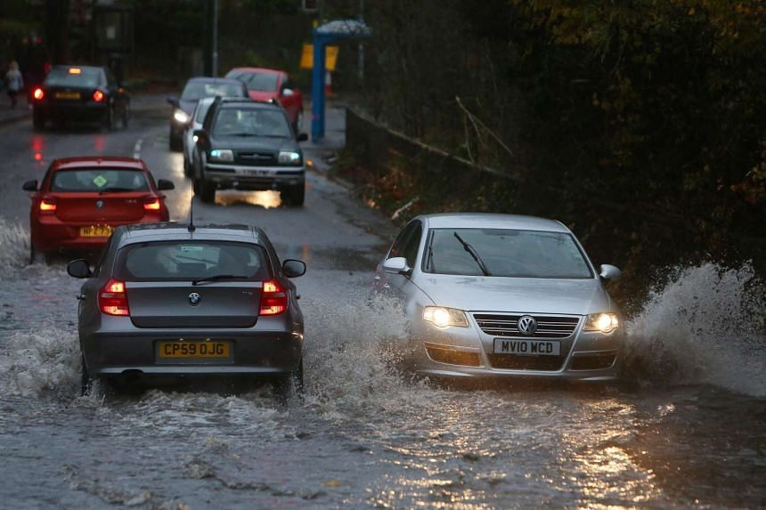 Cars drive on a flooded street outside Port Talbot, south Wales, Britain on Nov 21, 2016.