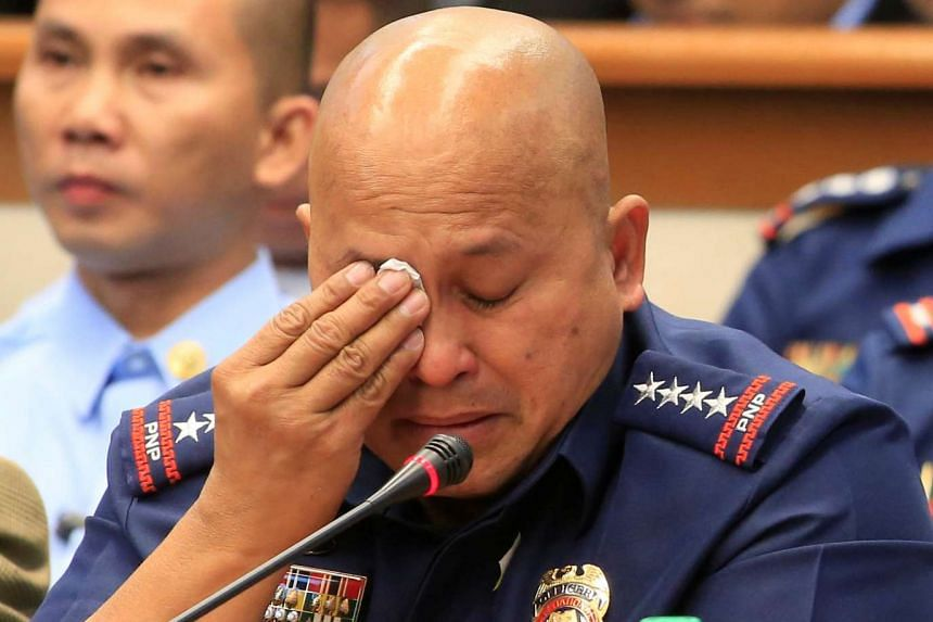 Philippine National Police chief Ronald Dela Rosa wipes his tears after answering questions at the Senate headquarters in Pasay city on Nov 23, 2016.