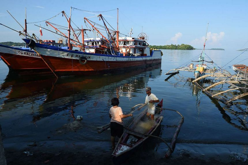 A fisherman and his wife fixing their nets next to a fishing fleet at the port in Masinloc in Zambales province.