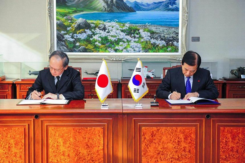 South Korean Defense Minister Han Min-koo (right) and Japanese Ambassador to South Korea Yasumasa Nagamine (left) signing the General Security of Military Information Agreement on the sharing of military intelligence on North Korea.