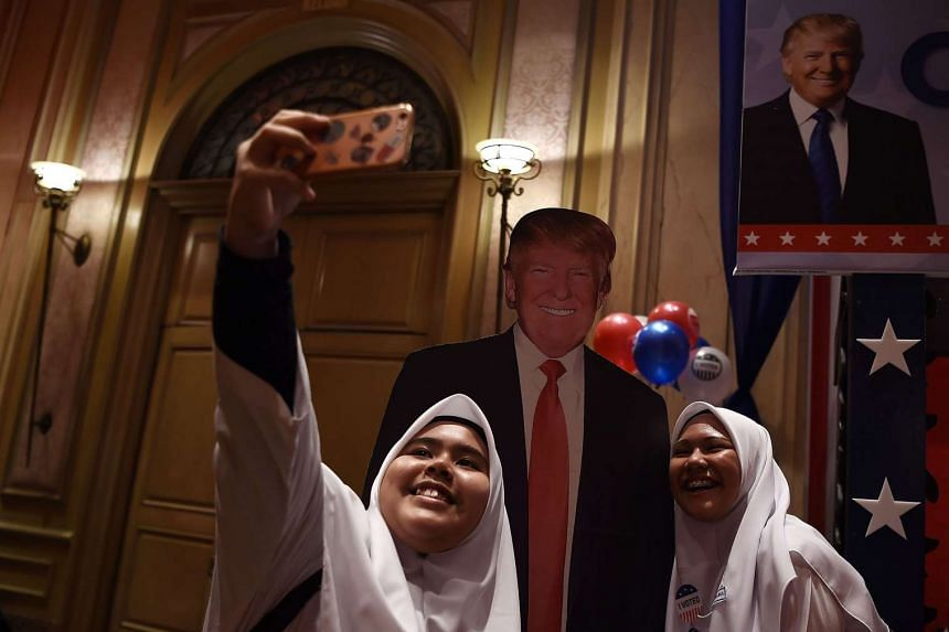 Malaysian Muslim schoolgirls taking a selfie with a cut-out of Mr Trump. Malaysia's best hope is that the incoming US President's anti-Muslim campaign rhetoric does not translate into official policy.
