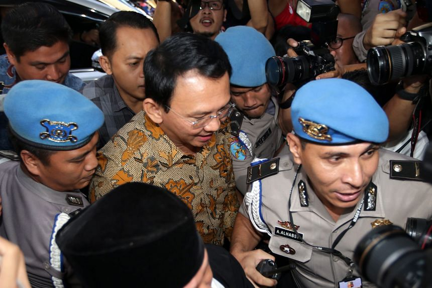 Ahok (centre) being escorted by police officers yesterday as he arrived at the National Police headquarters in Jakarta. The Jakarta governor was questioned by the police over his alleged insult of the Quran, a criminal offence that carries a jail sen