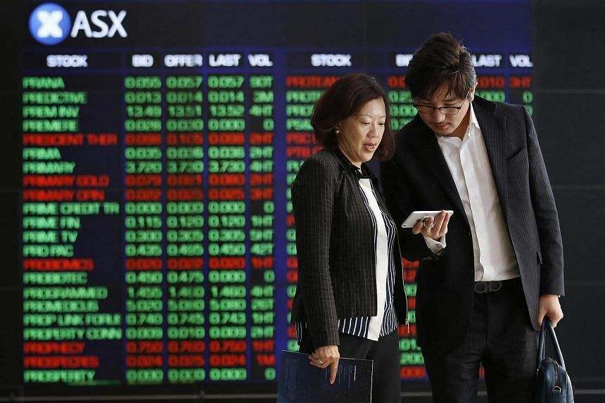 People look at a smartphone in front of electronic boards displaying stock information inside the Australian Securities Exchange.