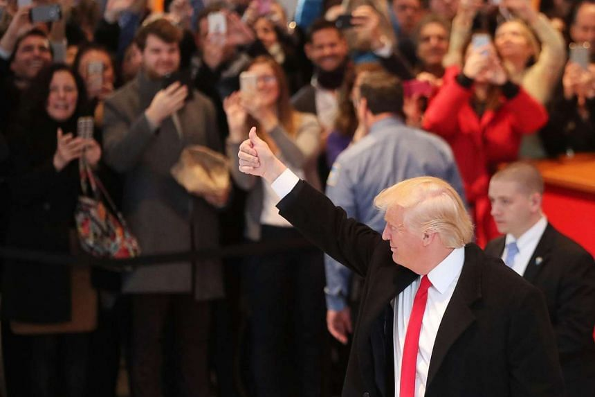 President-elect Donald Trump gives a thumbs up to the crowd as he walks through the lobby of the New York Times following a meeting with editors at the paper on Nov 22, 2016 in New York City.
