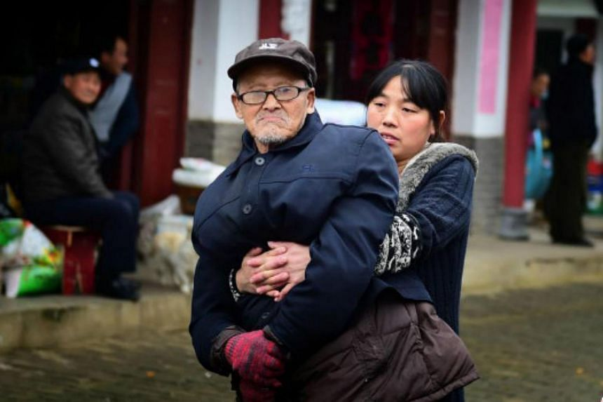 Ms Liu Qinxia brings her paralysed father out for a walk three times a day.