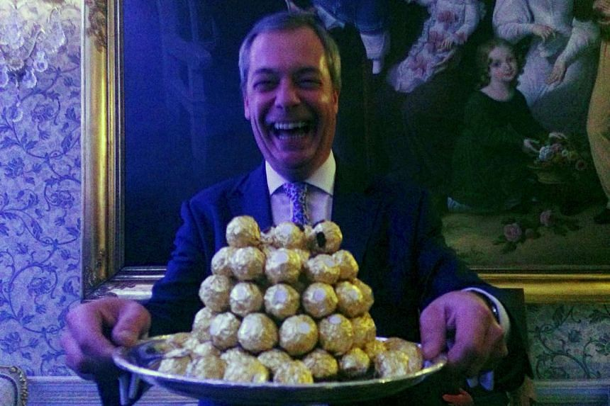 Nigel Farage, the interim leader of the United Kingdom Independence Party, holds a platter of Ferrero Rocher chocolates during a party in London on Nov 23, 2016.