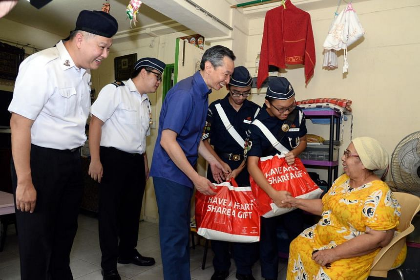 President of Boys Brigade Singapore Professor Ho Yew Kee with his son Mr Ho Yi Shyan, chairman of Boy's Brigade Share-a-Gift (BBSG) project Mr Lui Chong Chee, and two other BB members, handing out food hampers to Madam Zainubi Abdul Majid on Dec 18,