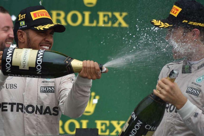 Lewis Hamilton (left), and Nico Rosberg celebrate on the podium in the Formula One Grand Prix of Brazil in Sao Paulo on Nov 13, 2016.