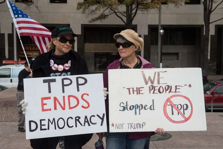 People hold signs as they demonstrate against the Trans-Pacific Partnership (TPP) trade agreement in Washington, DC on Nov 14, 2016.