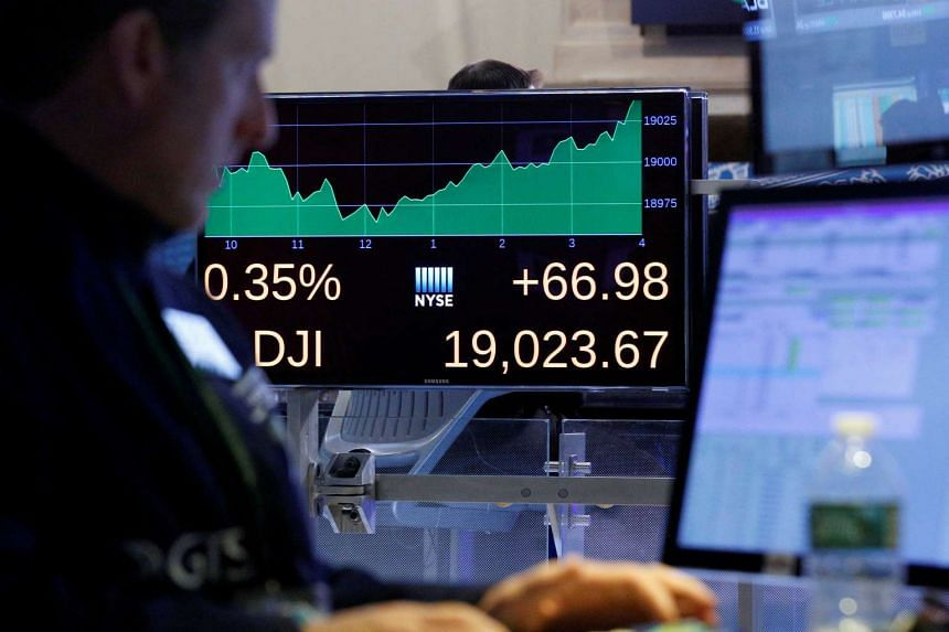 A trader works inside a post as a screen shows the Dow Jones Industrial Average after the close of trading on the floor of the New York Stock Exchange in New York City on Nov 22, 2016.