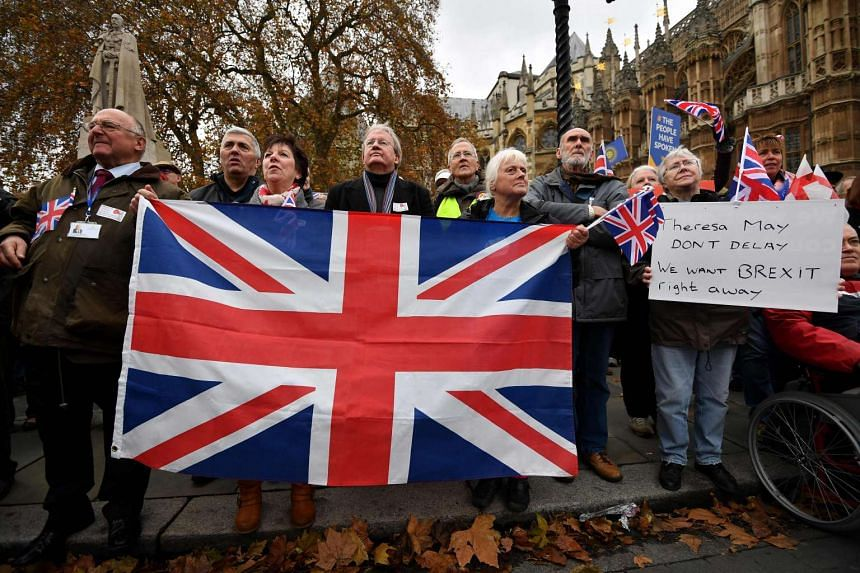 Protestors hold placards and a Union Flag during an anti-European Union (EU) demonstration outside the Houses of Parliament in London.