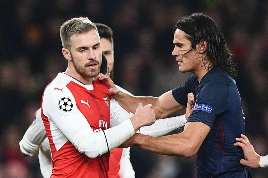 Paris Saint-Germain's Uruguayan forward Edinson Cavani (right) scuffles with Arsenal's Welsh midfielder Aaron Ramsey (left) after Arsenal were awarded a penalty.